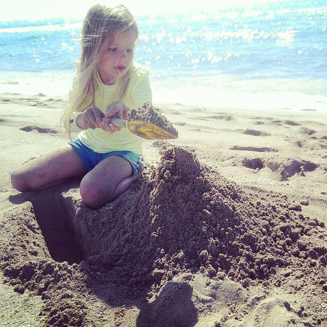 8yr old girl on beach digging sandcastles italy